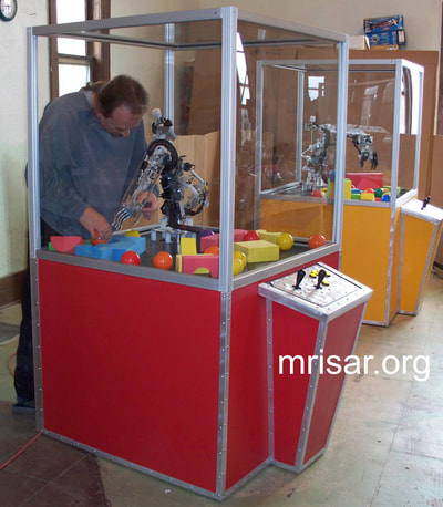 MRISAR's Team member installing our base mounted 5 and 3 Finger Robotic Arms into the exhibit cases we made. We have been making exhibit robotics since 1991.