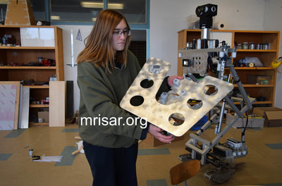 MRISAR Team member Aurora Siegel holding one of our larger Mars Probe Rovers in its early stage of fabrication!