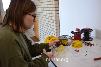 MRISAR's Team member Aurora Siegel fabricating Robotic Arm exhibits.