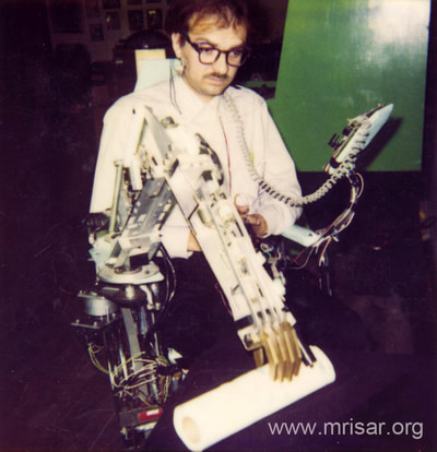 "MRISAR's Rehabilitation Robotics; Artificial Autonomics & Robotic Interface, For Paralysis Victims Designed & built in 1998, in 2 weeks. It is a ""Facial Feature Controlled Robotic Device"". John Siegel, the main inventor of this device is shown using it."