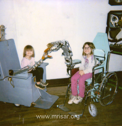 "MRISAR's Rehabilitation Robotics; seen here are two early prototype wheelchairs. The left is controlled by neck movements and the right one is an Artificial Autonomics & Robotic Interface, For Paralysis Victims Designed & built in 1998, in 2 weeks. It is a ""Facial Feature Controlled Robotic Device"". They are being used by MRISAR R&D Team Members. From left; Aurora and Autumn Siegel."