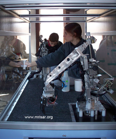 MRISAR's R&D Team members Autumn and Aurora prepping a finished Dual Combo Robotic Arm exhibit.