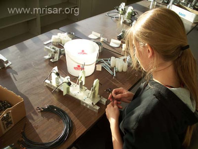 MRISAR's R&D Team member Autumn assembling robotic arms.