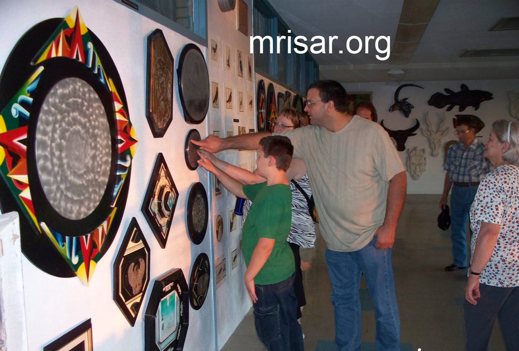 "Visitors to MRISAR are seen  here touching the etched Braille poem that accompanies ""Siren in Metal"" an original etched aluminum wall hanging sculpture by Victoria Lee Croasdell, an awarded, published and exhibited; multi-disciplined artist, photographer, writer, poet and engineer.  This piece is made of a hand etched aluminum mounted on M.D.O. that is painted with acrylic. Size 18"" wide x 15"" high, created in 1996. It is based on European mythology. Its etched aluminum oval poem in braille accompanies it to complete its total form as Illustrated Poetry. Victoria, a multi-awarded poet, writes poetry for all her art pieces and many of her photography pieces, thus adding an extra dimension or understanding into her conception of its particular creation."